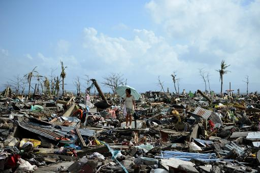 A survivor walks among the debris of houses destroyed by Super Typhoon Haiyan in Tacloban on the eastern Philippine island of Leyte on November 11, 2013 (AFP, Noel Celis)